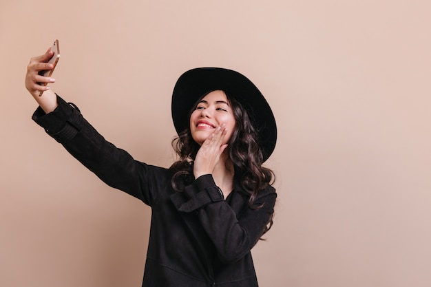 Romantische aziatische vrouw in jas selfie te nemen. studio shot van geïnspireerde chinese vrouw in hoed.