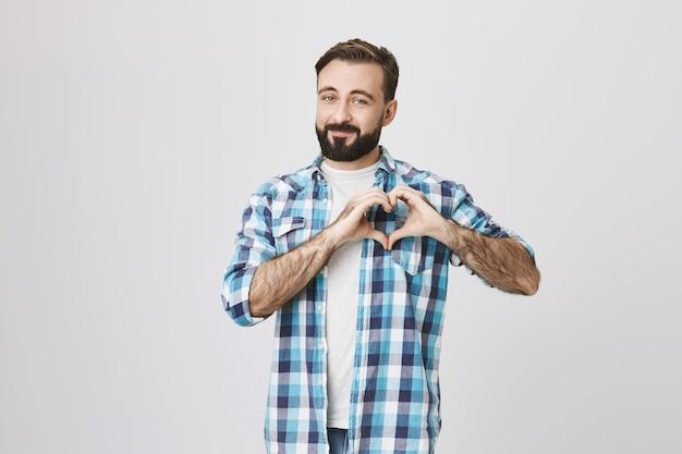 Romantische bebaarde man hart teken tonen, liefde uitdrukken