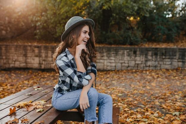 Romantische blanke vrouw met lang bruin haar wegkijken met dromerige glimlach, poseren in zonnige herfstdag