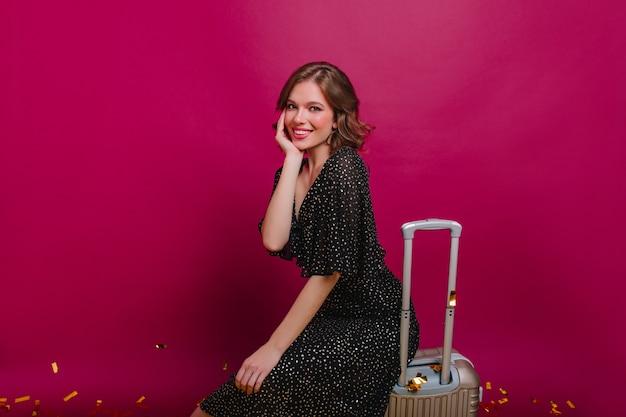 Romantische blonde meisje, zittend op een koffer en zachtjes haar gezicht aan te raken