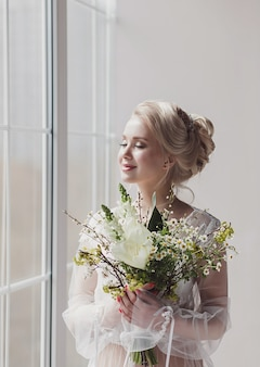 Romantische bruid met bruidsboeket bij raam wachtende bruidegom