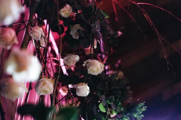 Romantische bruiloft tafelblad layout decor met grote weelderige bloemenboeketten waaronder witte rozen, ranonkels, perzische boterbloemen, witte orchideeën en kaarsen. hoge kwaliteit foto