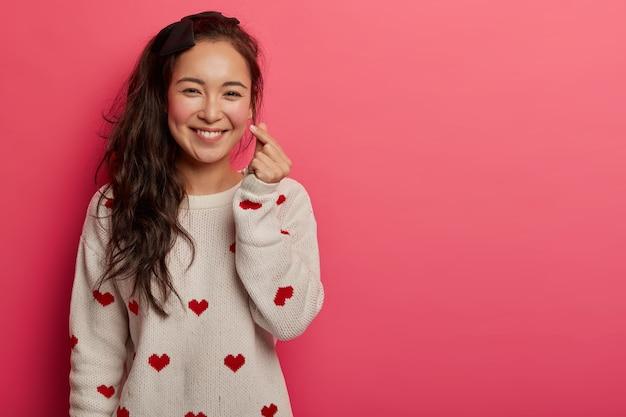Romantische chinese vrouw toont koreaans hartteken met twee gekruiste vingers, glimlacht vreugdevol en bekent verliefd, drukt genegenheid uit, draagt trui met hartprint, geïsoleerd op roze studiomuur