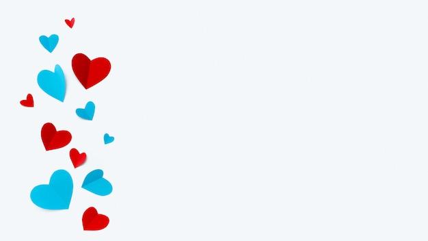 Romantische compositie gemaakt met rode harten op witte achtergrond met copyspace voor tekst