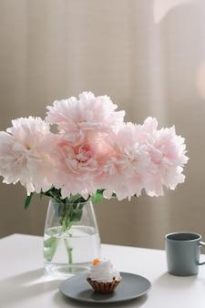 Romantische compositie met mooie roze pioenrozen in een vaas en een kopje koffie in huis interieur