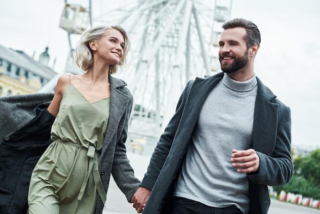 Romantische date buitenshuis jong stel rennend in het amusementspark, hand in hand kijkend naar elkaar