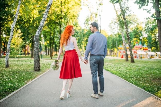 Romantische date, liefde paar lopen samen in zomer park, achteraanzicht. attracrive vrouw met bloemen en jonge man vrije tijd buitenshuis