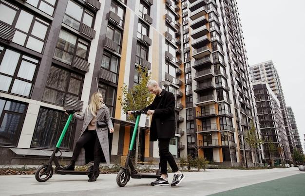 Romantische date op e-scooters! gelukkige vrouw met blond haar en man in vrijetijdskleding goed tijd doorbrengen rijden op gehuurde elektrische scooters en lachen. flatblokken op achtergrond.