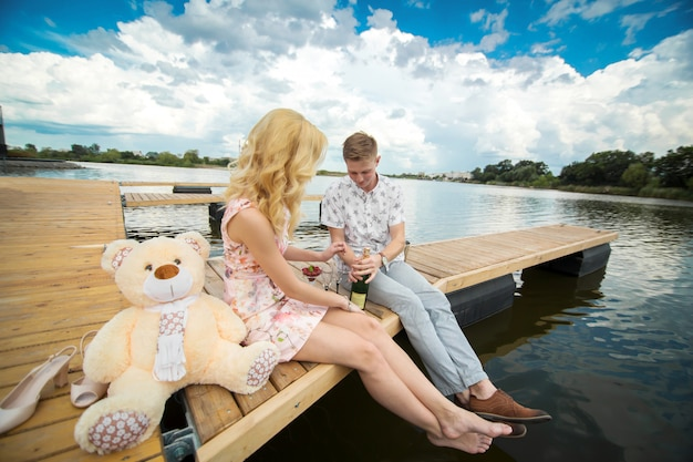Romantische date verrassing. een jonge man en een meisje op een houten pier. de man opent de champagne.