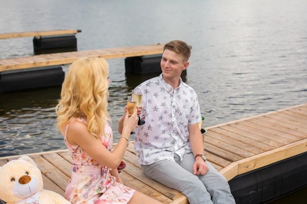 Romantische date verrassing. een jonge man en een meisje op een houten pier. hef glazen op met champagne.