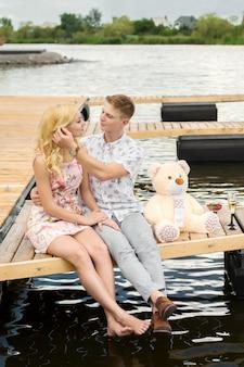 Romantische date verrassing. een jonge man en een meisje op een houten pier. knuffel en kus zittend op de pier. romantisch liefdesverhaal