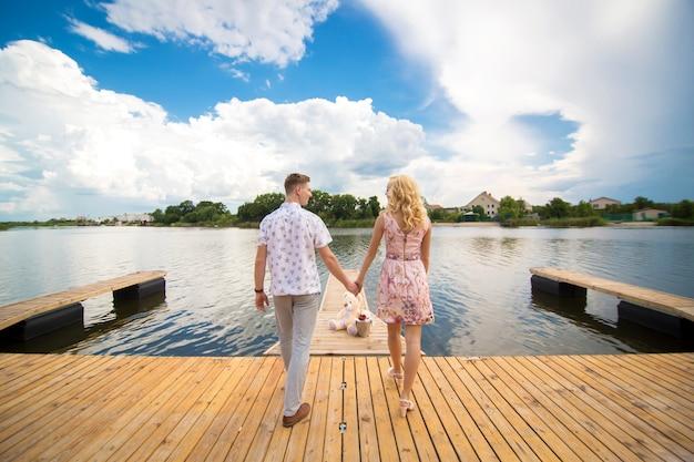Romantische date verrassing. een jonge man en een meisje op een pier met uitzicht op het meer. de man geeft het meisje een teddybeer.