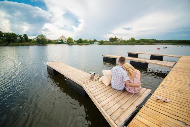 Romantische date verrassing. jonge kerel en een meisje op een houten pier. knuffel en kus zittend op de pier. romantisch liefdesverhaal