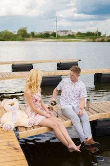 Romantische date verrassing. jonge kerel en een meisje op een houten pier. man giet champagne in de glazen.