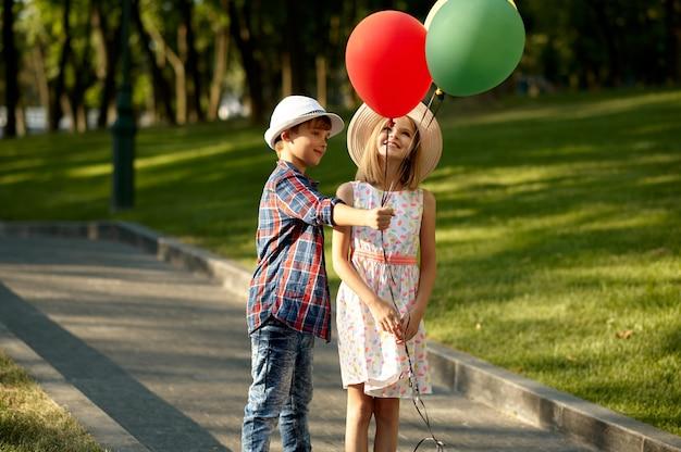 Romantische date voor kinderen in het zomerpark, vriendschap, eerste liefde. jongen en meisje lopen met luchtballonnen. kinderen hebben plezier buitenshuis, kindertijd