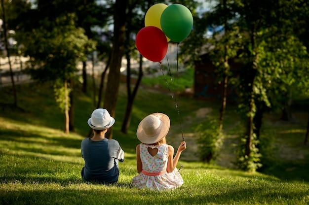Romantische date voor kinderen in het zomerpark, vriendschap, eerste liefde. jongen en meisje met luchtballonnen zittend op een gras. kinderen hebben plezier buitenshuis, gelukkige jeugd