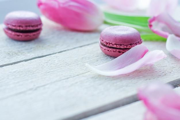 Romantische delicate compositie met roze bloemen en bitterkoekjes.