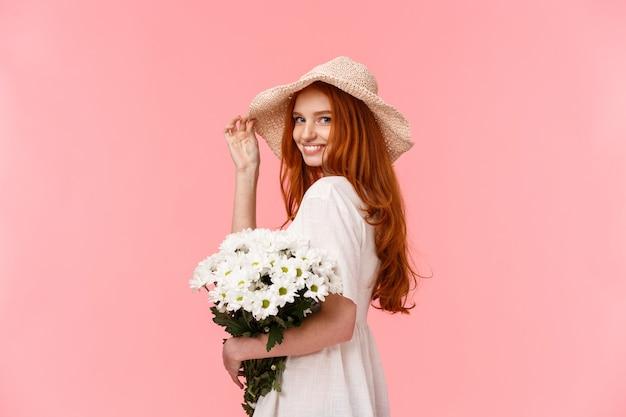 Romantische, domme en tedere vrouwelijke roodharige vrouw in schattige hoed, jurk, boeket witte bloemen vasthouden, camera draaien en koket glimlachen, flirten met vriendje over roze