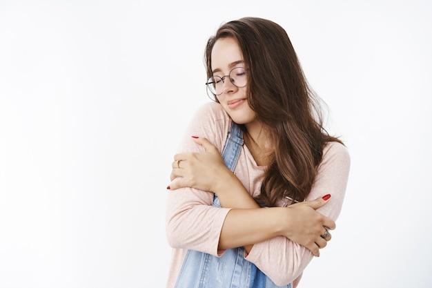 Romantische dromerige knappe vrouw die zichzelf omhelst met gesloten ogen, leunend op de schouder, nostalgisch gevoel
