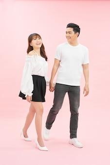 Romantische echtgenoten op vakantie huwelijksreis gaan lopen houden hand voelen tevreden vrolijk dragen denim jeans vooruitzicht geïsoleerd over roze kleur achtergrond