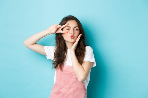 Romantische en mooie jonge vrouw die luchtkus verzendt, lippen plooit en v-teken vredesgebaar toont dichtbij oog, die zich over blauwe achtergrond bevindt.