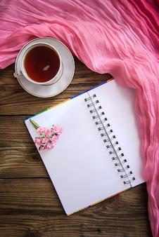 Romantische foto met kladblok, thee en roze bloemen