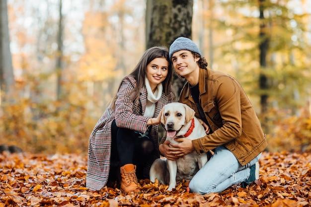 Romantische gelukkige paar verliefd genieten van hun tijd met labrador in herfst park