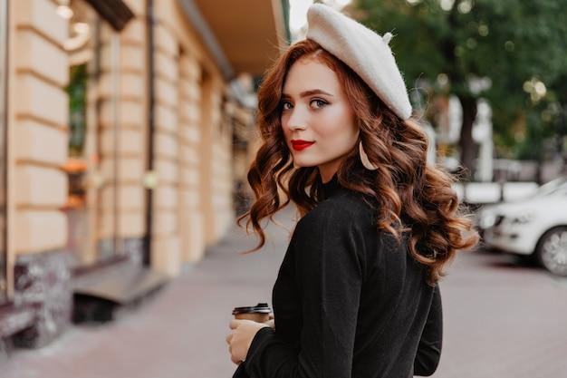 Romantische gembervrouw die in franse baret terugkijkt. buiten foto van schattige brunette meisje genieten van herfstdag.