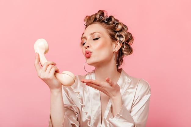 Romantische huisvrouw in haarkrulspelden op haar hoofd en licht gewaad stuurt een kus op de telefoon