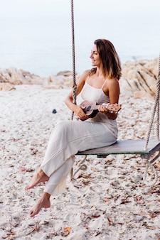 Romantische jonge gelukkig rustige blanke vrouw met ukelele op tropisch rotsachtig strand bij zonsondergang