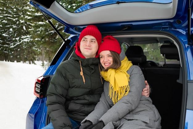 Romantische jonge hipster paar knuffelen zittend in de kofferbak van de auto. liefde, valentijnsdag