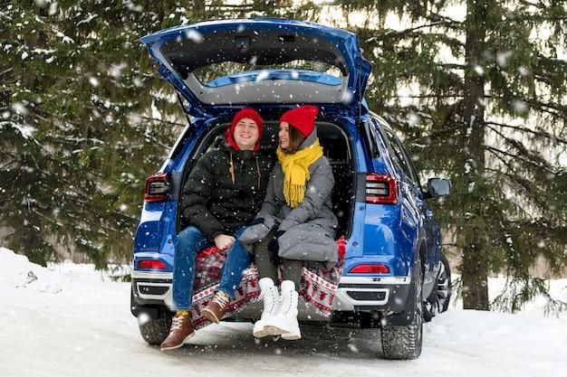 Romantische jonge hipster paar knuffelen zittend in de kofferbak van de auto onder vallende sneeuw