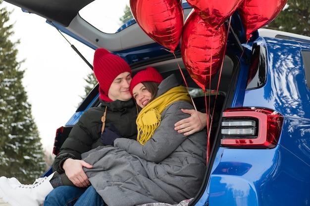 Romantische jonge hipster paar knuffelen zittend in de kofferbak van de auto