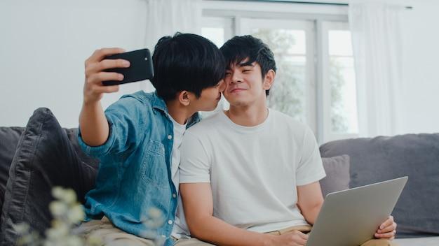 Romantische jonge homo paar grappige selfie door mobiel thuis. aziatische mannelijke minnaar lgbt ontspant gelukkig pret gebruikend technologie mobiele telefoon die samen een foto glimlachen terwijl het liggen bank in woonkamer.