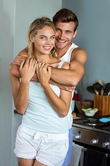 Romantische jonge man die vrouw van erachter in keuken omhelst