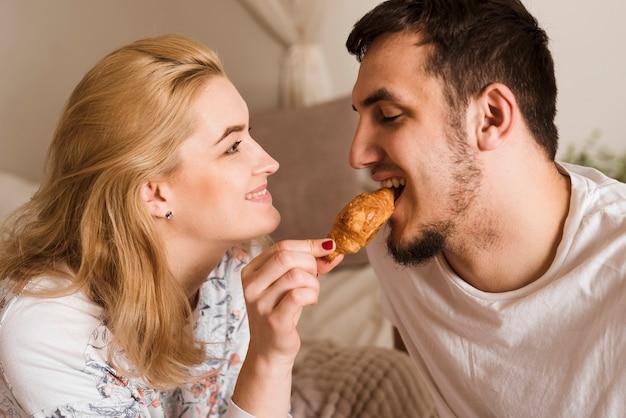 Romantische jonge man en vrouw die een croissant delen