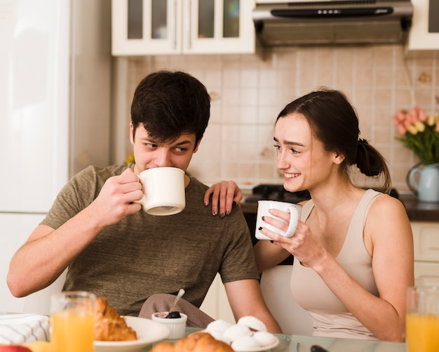 Romantische jonge man en vrouw die ontbijt hebben