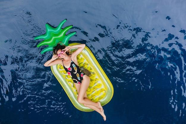 Romantische jonge vrouw rusten in zwembad in warme zomerdag. overhead portret van blije europese dame in zonnebril en zwembroek.