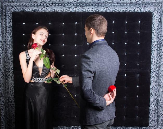 Romantische jongeman die een beeldschone jonge vrouw in een elegante zwarte cocktailjurk ten huwelijk vraagt en haar een roos overhandigt voordat hij de ring produceert