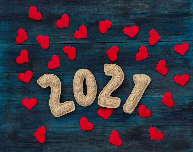 Romantische kerstmisachtergrond met gebreid aantal en rode harten pandemisch nieuwjaar