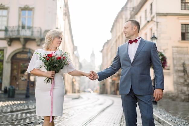 Romantische knappe man en mooie vrouw, gekleed in elegante kleding, genietend van stadswandeling. portret van een gelukkig verliefd stel van middelbare leeftijd, hand in hand, een date in de oude stad