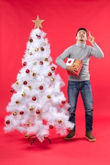 Romantische knappe volwassene in een grijze blouse die zich dichtbij de verfraaide witte kerstboom bevindt