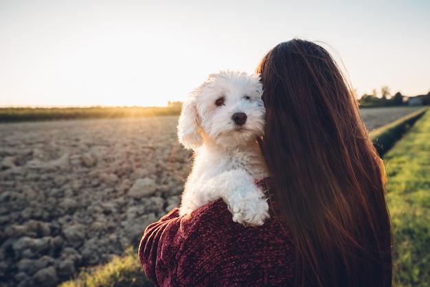 Romantische knuffel tussen een witte hond en zijn eigenaar. mens en dier verliefd