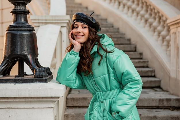 Romantische lachende stijlvolle vrouw poseren in winter herfst mode trend blauwe puffer jas en hoed baret in oude mooie straat trappen Gratis Foto