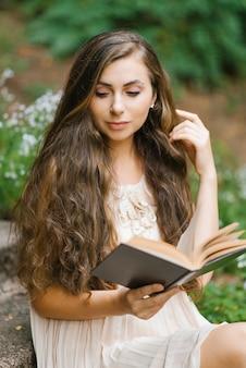 Romantische langharige jonge mooie vrouw die een boek leest