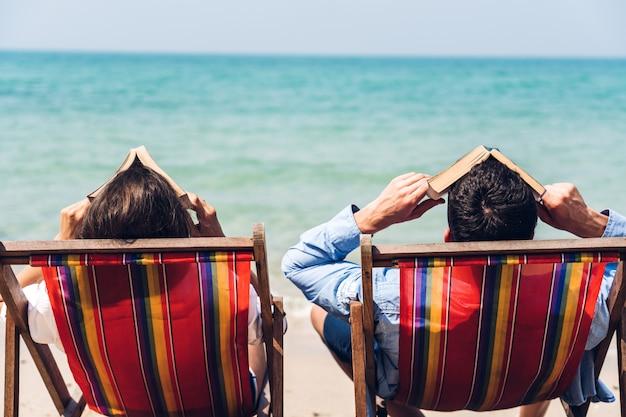 Romantische liefhebbers jong koppel ontspannen samen zitten op het tropische strand en op zoek naar de zee. zomervakanties Premium Foto