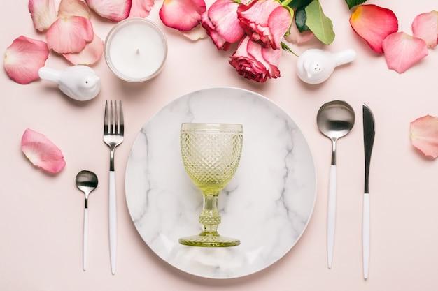 Romantische lijst die in roze kleuren plaatst. servies en decoraties voor het serveren van een feestelijke tafel