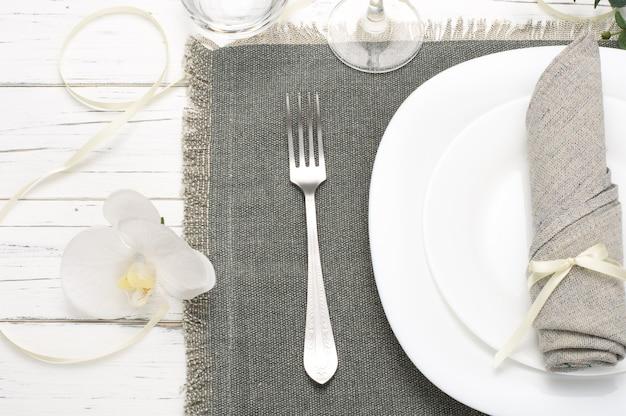 Romantische lijst die met orchidee en grijs servet op witte houten achtergrond plaatst