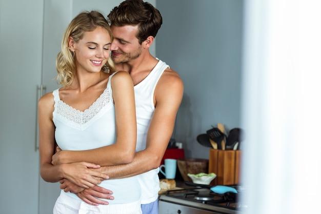Romantische man die vrouw van achter thuis omhelst