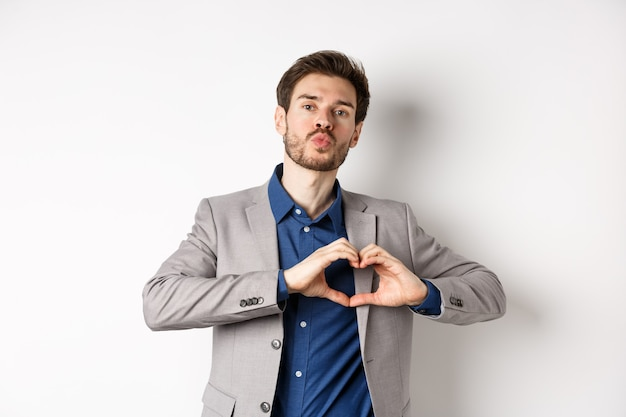 Romantische man in pak hart teken tonen en tuit lippen voor kus, liefde en passie uiten, net als zijn geliefde, staande op een witte achtergrond.